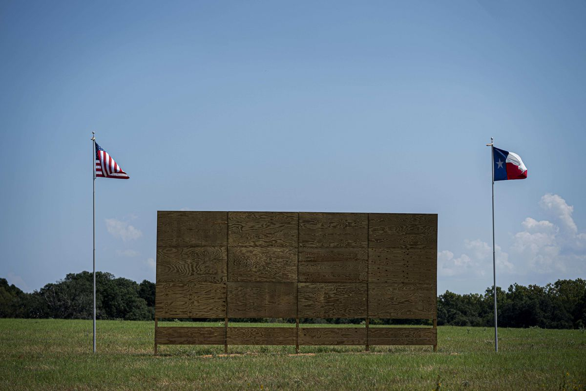 An empty billboard in a field flanked by flags on flagpoles.