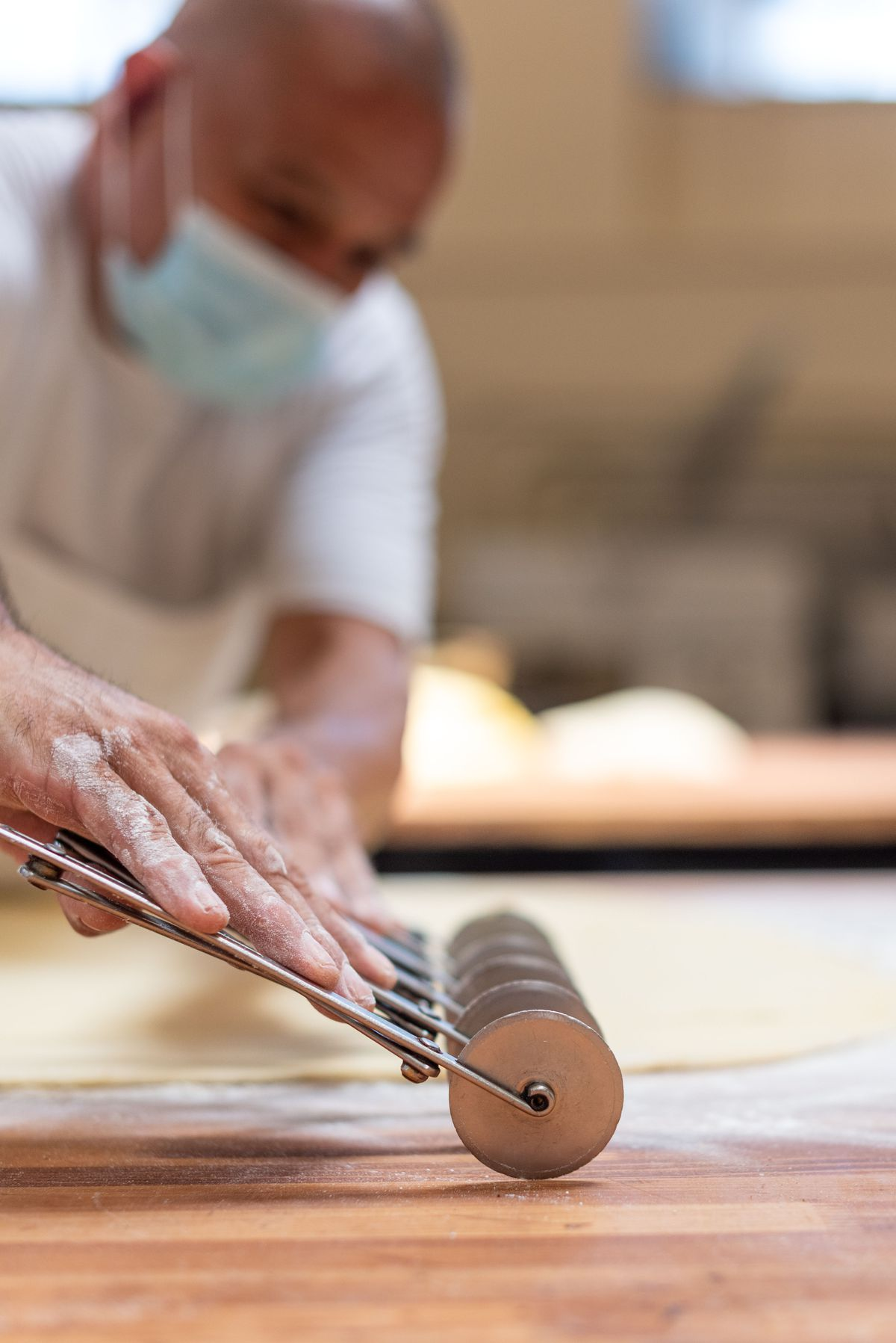 A close up of hands rolling cutters over a sheet of dough.