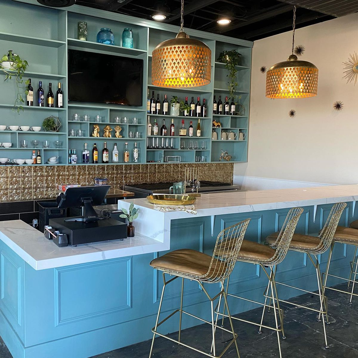 A bar with four high-top chairs. The bottom of the bar and back bar are blue. The counter is white. There is a cash register on the left.