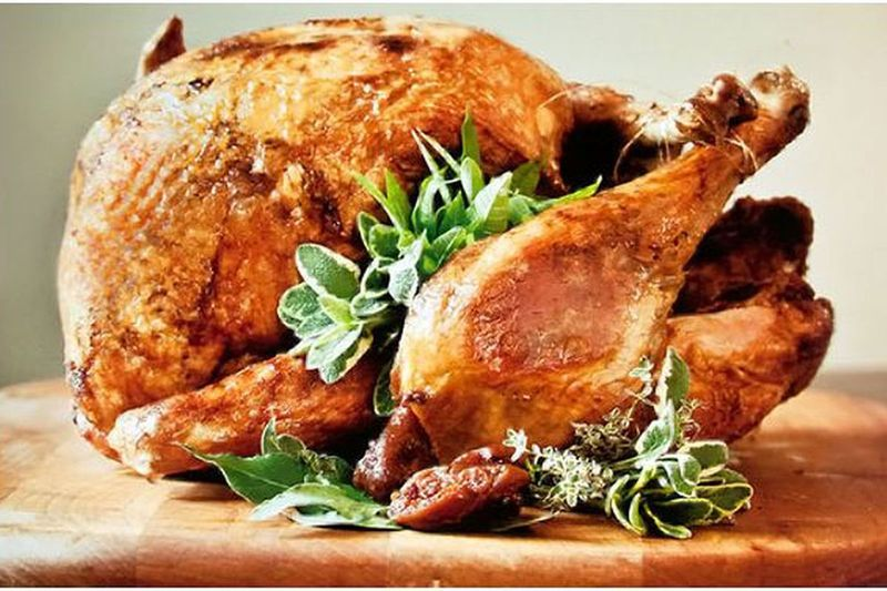 Deep-fried turkey decorated with sage on top of a wooden cutting board.