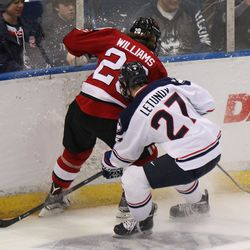 UConn's Max Letunov (27) battles with Northeastern's Eric Williams (20) for a puck in the corner.
