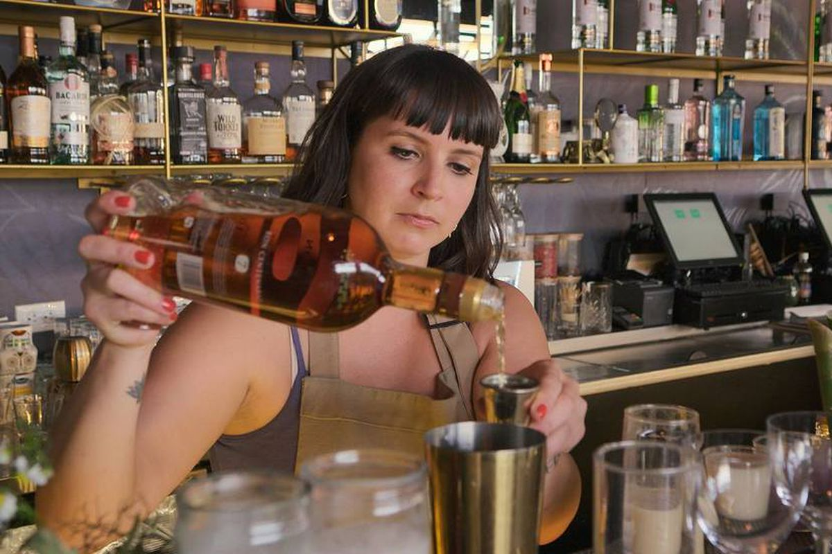 A bartender pours rum into a jigger held beside a cocktail shaker in front of a back bar filled with bottles