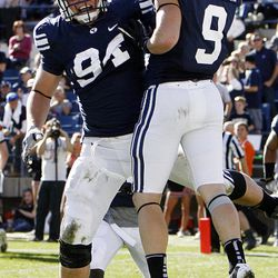 Brigham Young Cougars defensive back Daniel Sorensen, right, is congratulated after taking an interception back for a touchdown as Brigham Young University faces Idaho State in NCAA football in Provo, Saturday, Oct. 22, 2011.