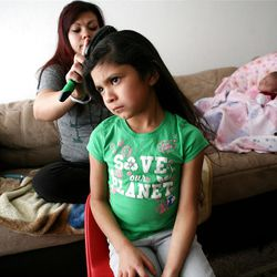 Adriana Carreon brushes her daughter Ariza's hair at home in Taylorsville on Saturday, Feb. 9, 2013. Carreron's family was recently evicted, but they managed to land on their feet.