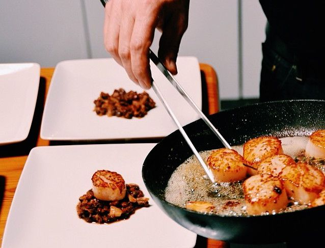 A hand uses tongs to transfer cooked scallops from a pan to austere plates