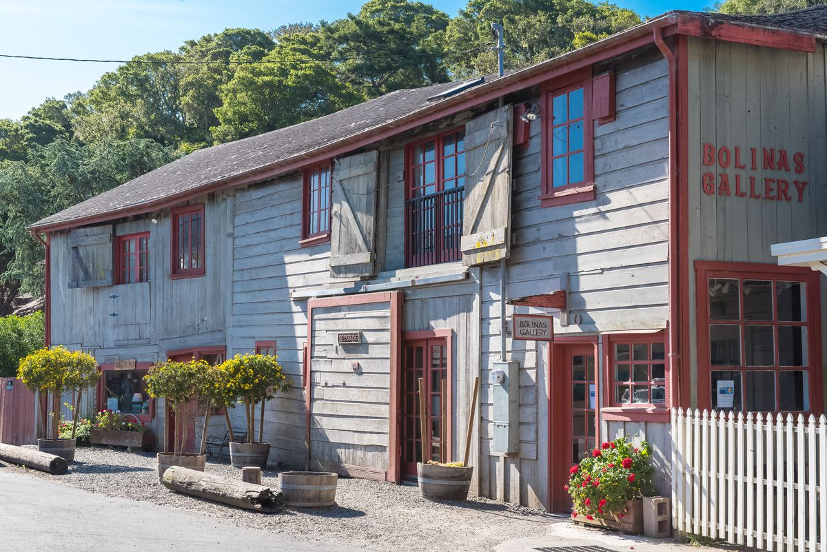 An old two-story building, the Bolinas Gallery, with horizontal wood paneling, ret trim, and a white picket fence.