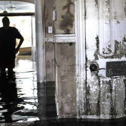 Don Duplantier walks through his flooded home as water recedes from Hurricane Isaac in Braithwaite, La., Sunday, Sept. 2, 2012. In the foreground is a sign marking the waterline from Hurricane Katrina, but floodwater from Isaac went all the way up to the second floor.