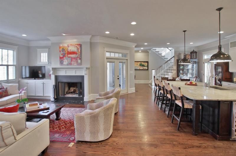 A large living room with white walls and much furniture.