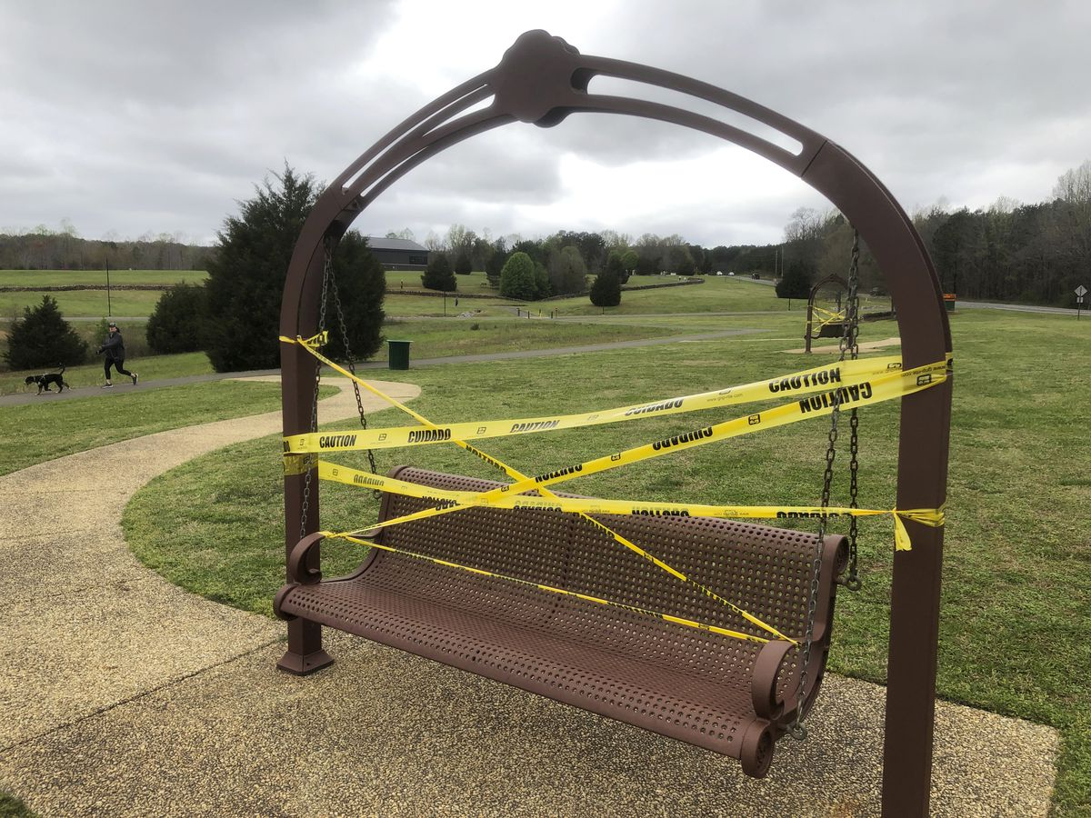 Caution tape covers swings and benches in a grassy open space park, while a man jogs with his black dog in the distance.