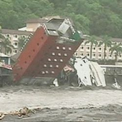 In this image made from television broadcast by ETTV television Sunday, Aug. 9, 2009, a a six-story hotel in Chihpen, Taitung county, Taiwan collapses and plunges into a river after floodwaters eroded its base as typhoon Morakot passed through the area.