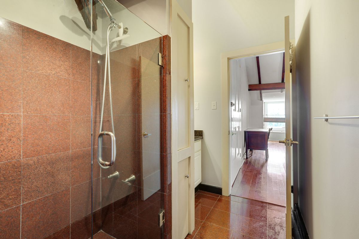 A glass shower with red tiles sits in a bathroom with a door open to reveal a desk and window in the next room.