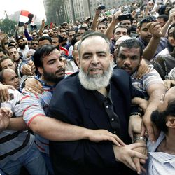 FILE - In this Oct. 28, 2011 file photo, Egyptian Muslim cleric and candidate for the Egyptian presidency Hazem Salah Abu Ismail, center, is surrounded by his supporters as he enters Tahrir Square , in Cairo, Egypt. The presidential election scheduled in May will mark the beginning of a handover of power by the ruling military to an elected civilian, following last year's popular uprising that overthrew Hosni Mubarak. (AP Photo/Amr Nabil, File)