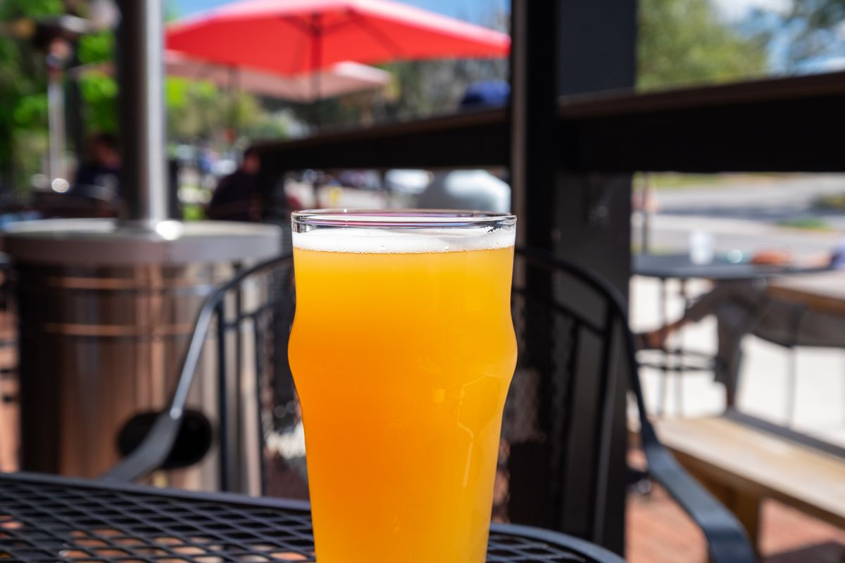 A tall cold clear beer glass filled with a sour flavour craft beer. The sun is shining on the glass and head of the beer. There are tables and umbrellas set up on a patio in the background.