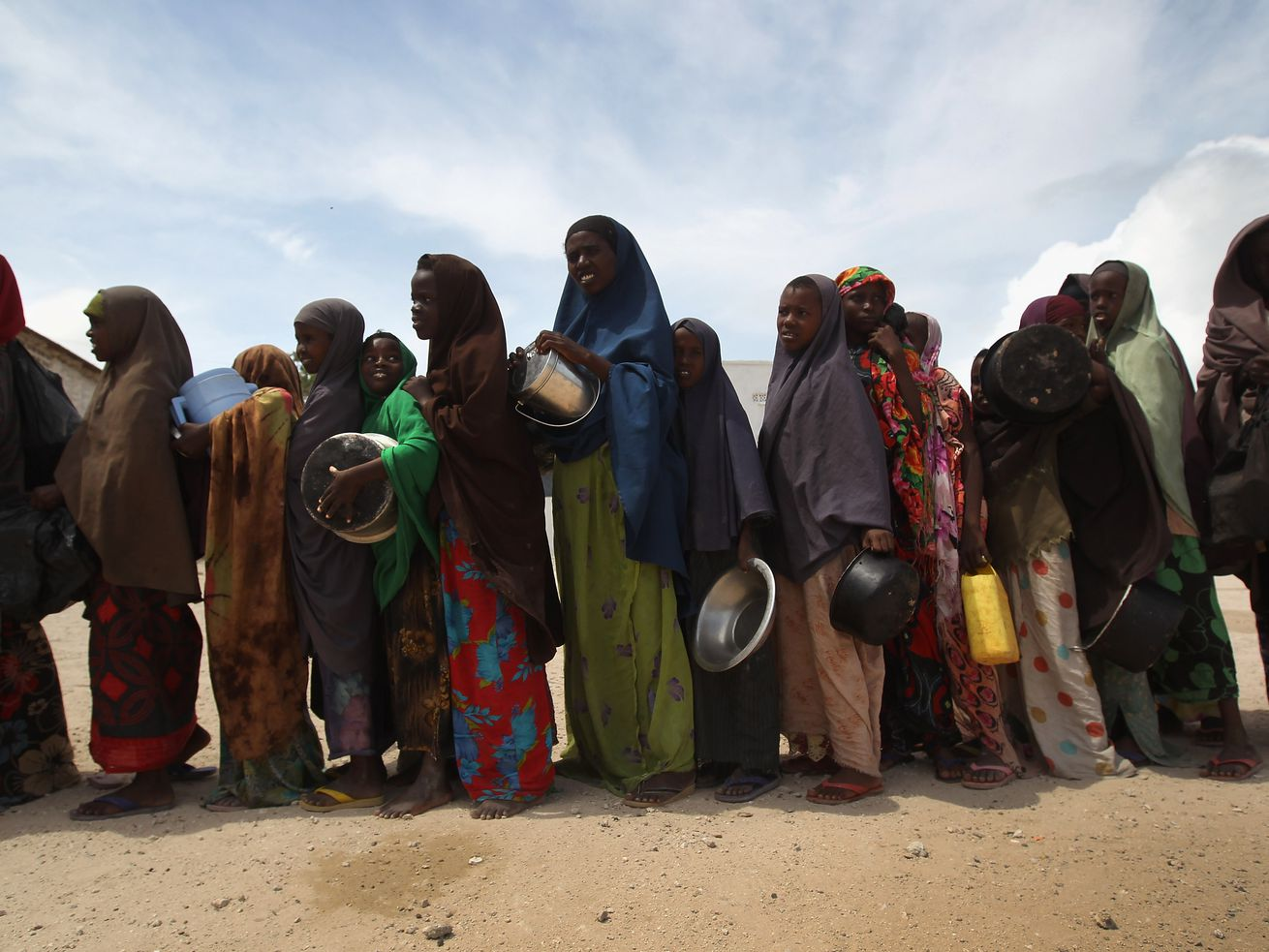 Women and children stand in line for food aid on August 14, 2011, in Mogadishu, Somalia.