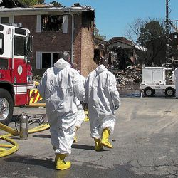 Investigators approach the damaged Mayfair Mews apartment complex in Virginia Beach, Va., on Saturday, April 7, 2012. The Navy and civilian authorities have just begun their investigation into the crash of the Navy F/A-18D fighter that hit the complex on Friday.