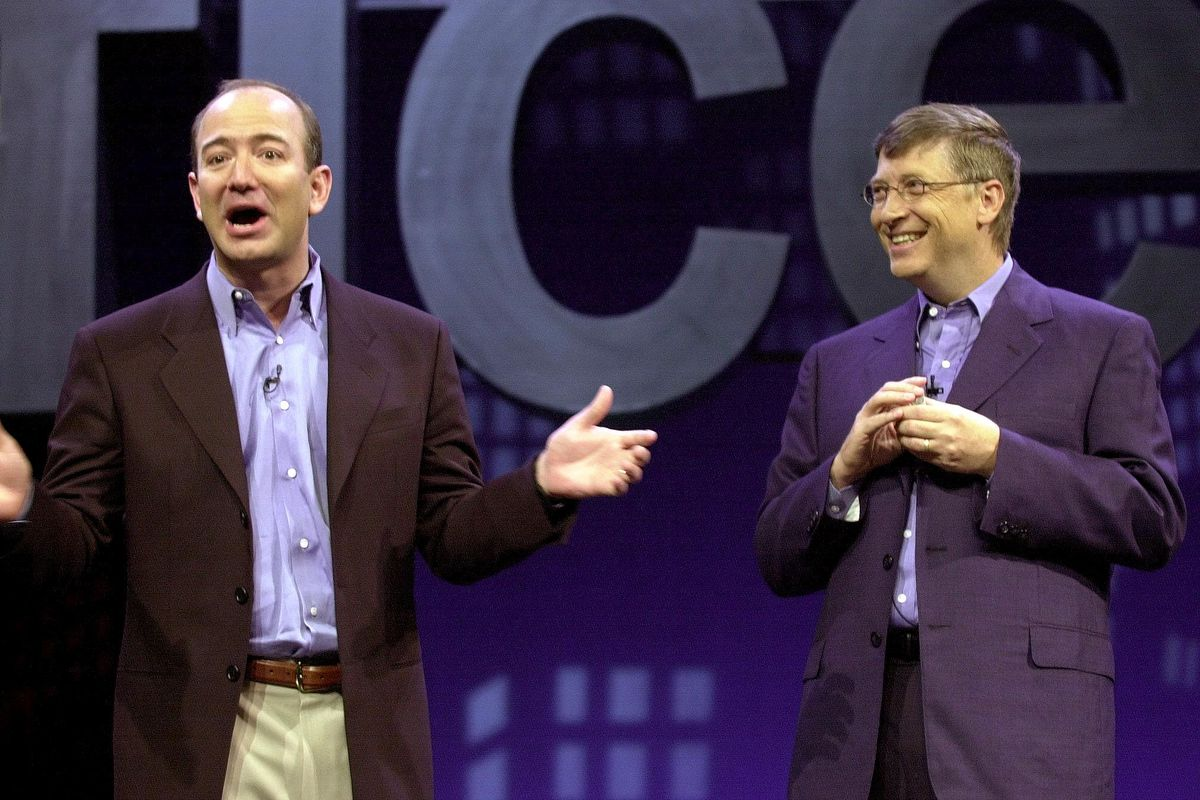 Amazon.com CEO Jeff Bezos (L) tells a joke with Mi