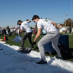 Students shovel snow to put in a wading pool for their version of the Polar Plunge at St. Patrick's High School in the Belmont Central neighborhood, Saturday morning, March 6, 2021.
