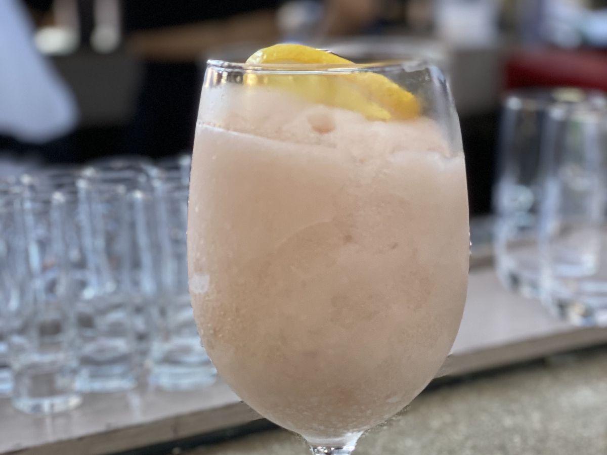 A peach pink slushee cocktail with a lemon slice