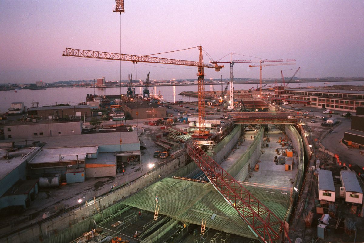 A wide shot of a major construction project, with a crane hovering over the site of the sinking of a highway underground.