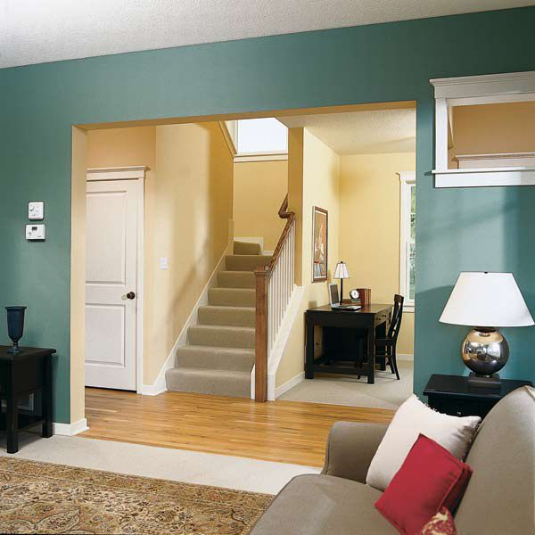 Open plan interior walls painted in two different colors, the living room is light blue and the entry way is yellow.
