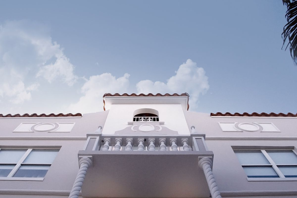A street-level photo looking up at a new spanish-style hotel in south beach