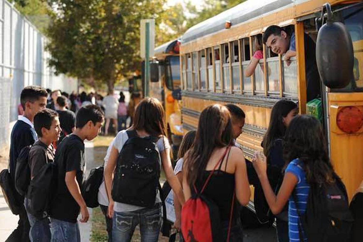 Rosando Martinez, 12, hangs his head out a school bus window and talks to friends after school at Grant Beacon Middle School in Denver.