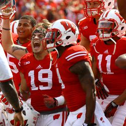 Safety Leo Musso, and other members of the Badgers jump around between the 3rd and 4th quarter