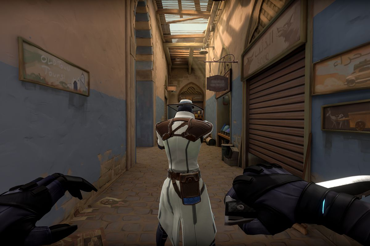 One player looks down a hallway in Valorant while another players sneaks up from behind