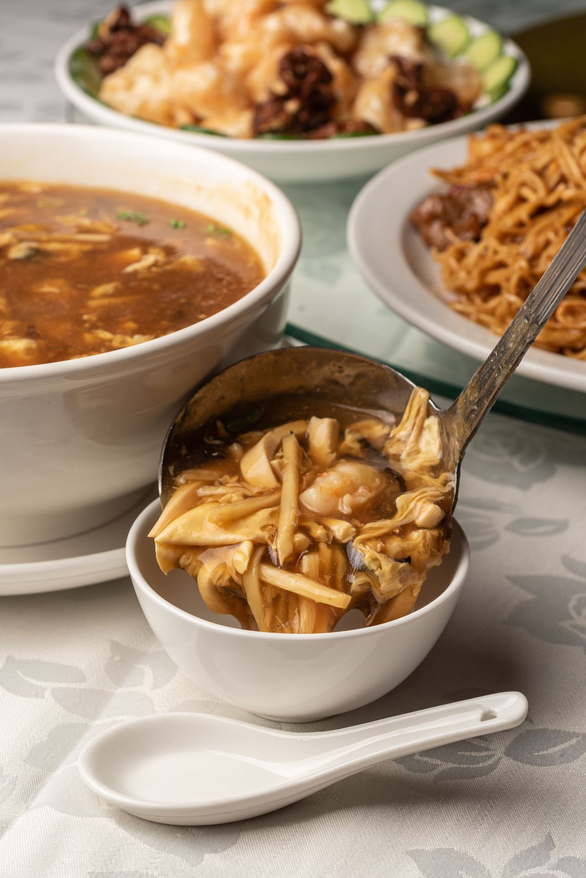 A ladle of hot and sour soup brimming with tofu and mushrooms.