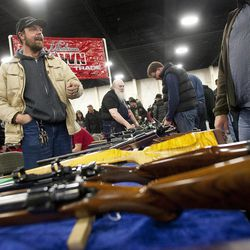 Hank Worthen, left, chats with potential customers at the South Towne Expo Center during the 2013 Rocky Mountain Gun Show, Saturday, Jan. 5, 2013.