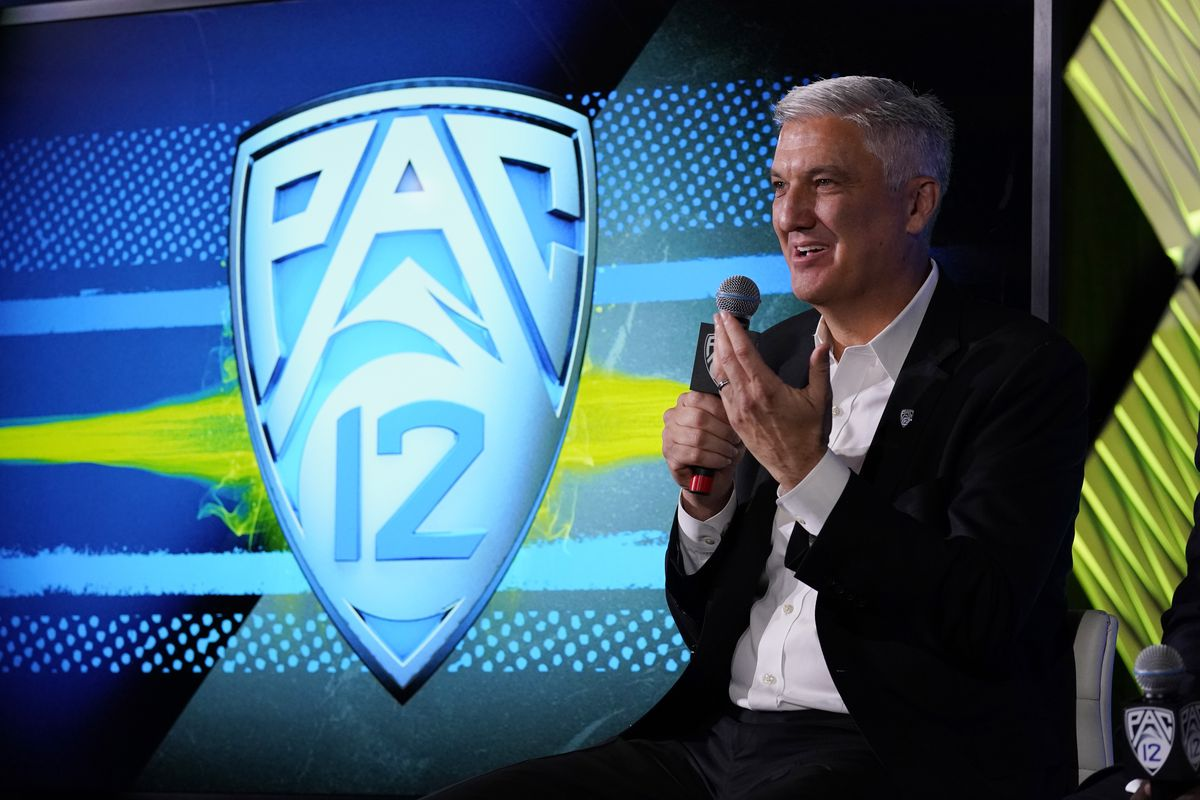 Pac-12 Commissioner George Kliavkoff sits on a chair holding a microphone