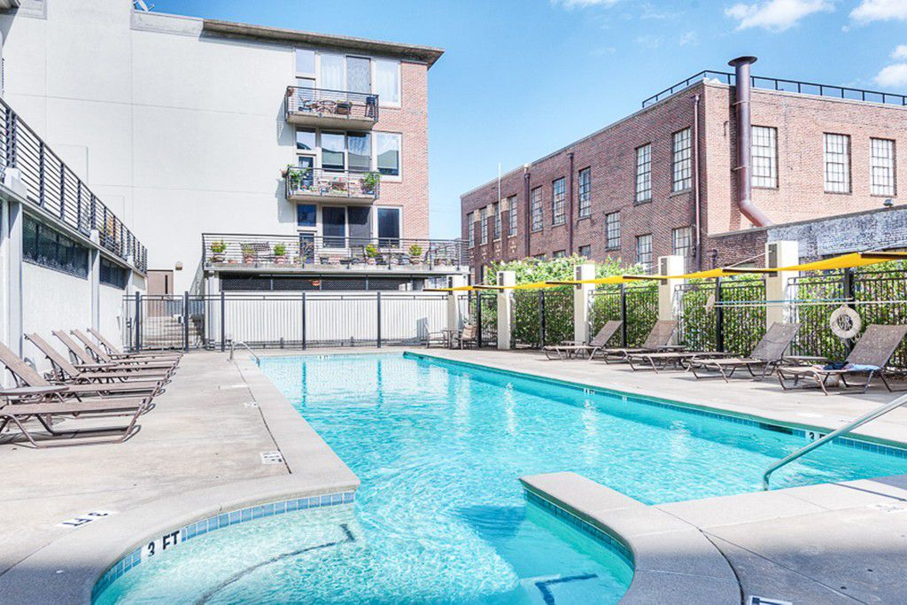 A large blue pool at a condo building.