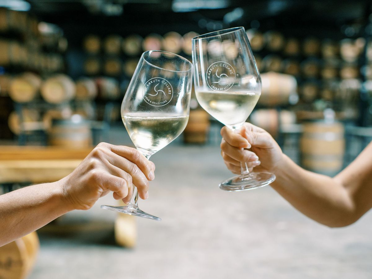 Two hands grasping the stems of wine glasses filled with white wine in a barrel room.