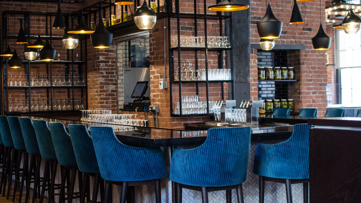 A restaurant bar in a high-ceilinged space with brick walls. The bar stools are a royal blue corduroy-like material.