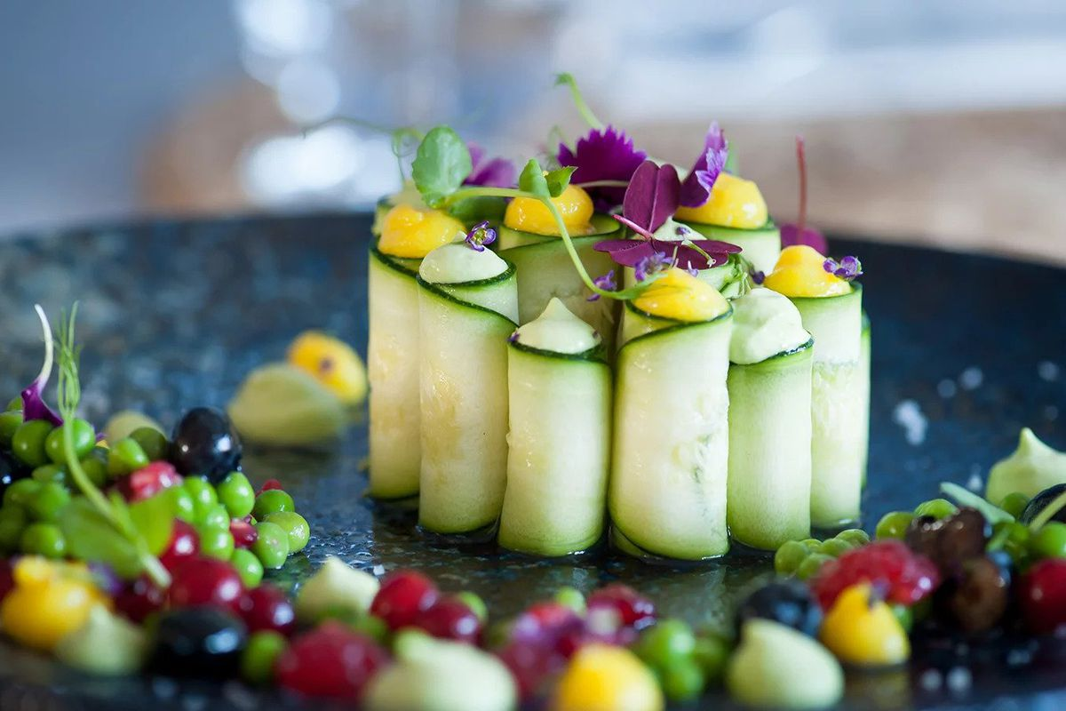 A dish composed of cucumbers sliced and rolled into cylinders topped with dollops of a yellow and pale green sauce and purple and green leaves