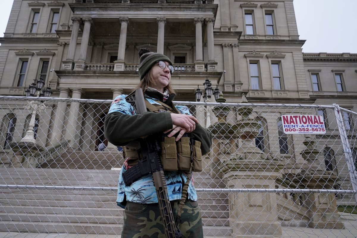 Timothy Teagan, a member of the Boogaloo Bois movement, stands with his rifle outside the state capitol in Lansing, Mich., Sunday, Jan. 17, 2021.