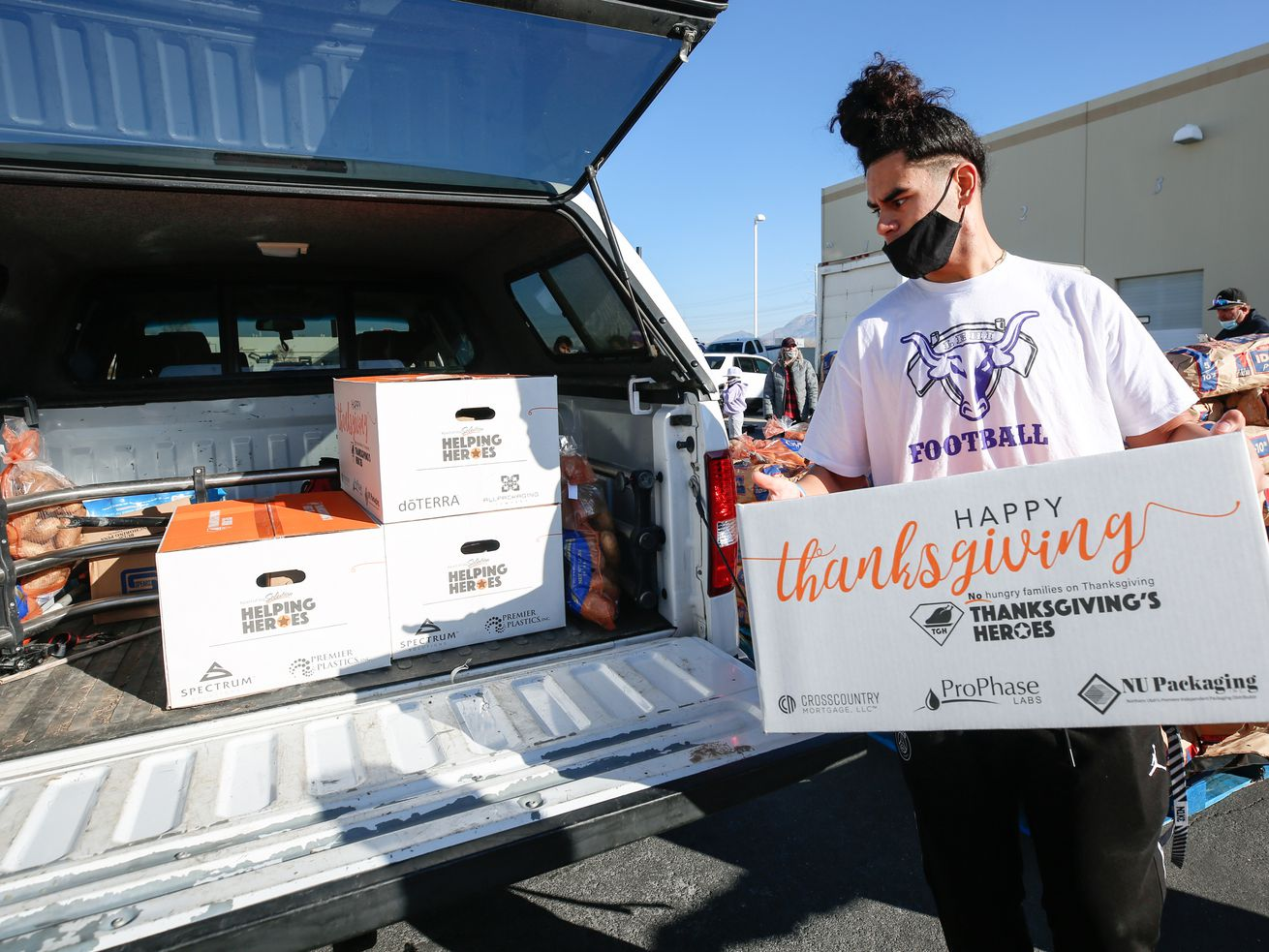 Josiah Westover, a Thanksgiving Heroes volunteer from Lehi High School, places a box of food into a car at Spectrum Solutions in Draper on Saturday, Nov. 21, 2020.