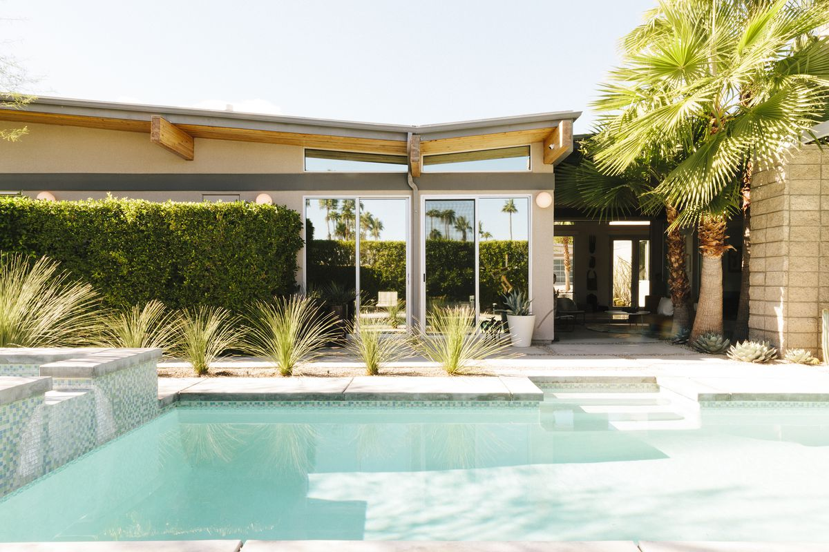 A swimming pool with light blue water is in the foreground. There is a house in the background with glass doors. A palm tree and other plants sit between the house and the swimming pool.