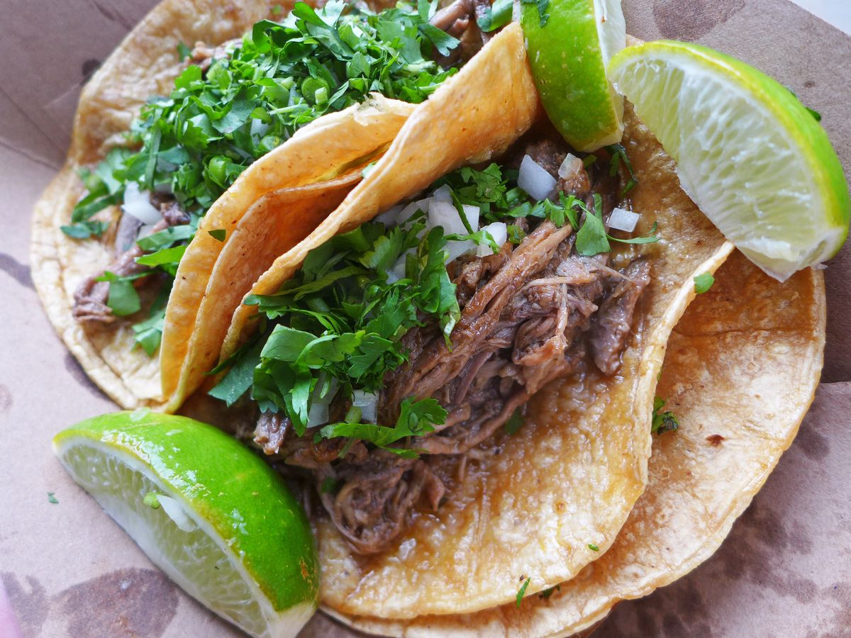 A pair of double tortilla birria tacos with a glimpse of the striated meat underneath chopped cilantro and onions.