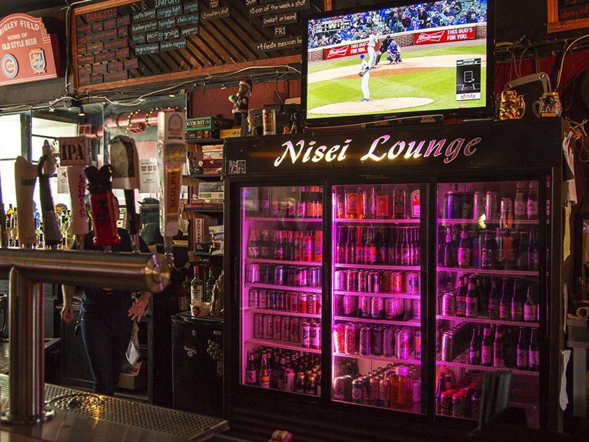 A purple-lit cooler inside a dive bar.