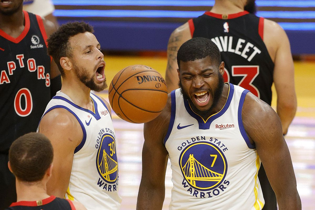 Stephen Curry and Eric Paschall of the Golden State Warriors react after Paschall made a shot and was fouled during their game against the Toronto Raptors at Chase Center on January 10, 2021 in San Francisco, California.