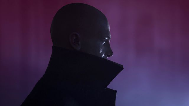 Profile image of bald man against a dark purple tinged background