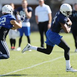 Brigham Young Cougars running back Riley Burt (34) runs from Brigham Young Cougars defensive back Hiva Lee (22) during practice in Provo on Wednesday, March 8, 2017.