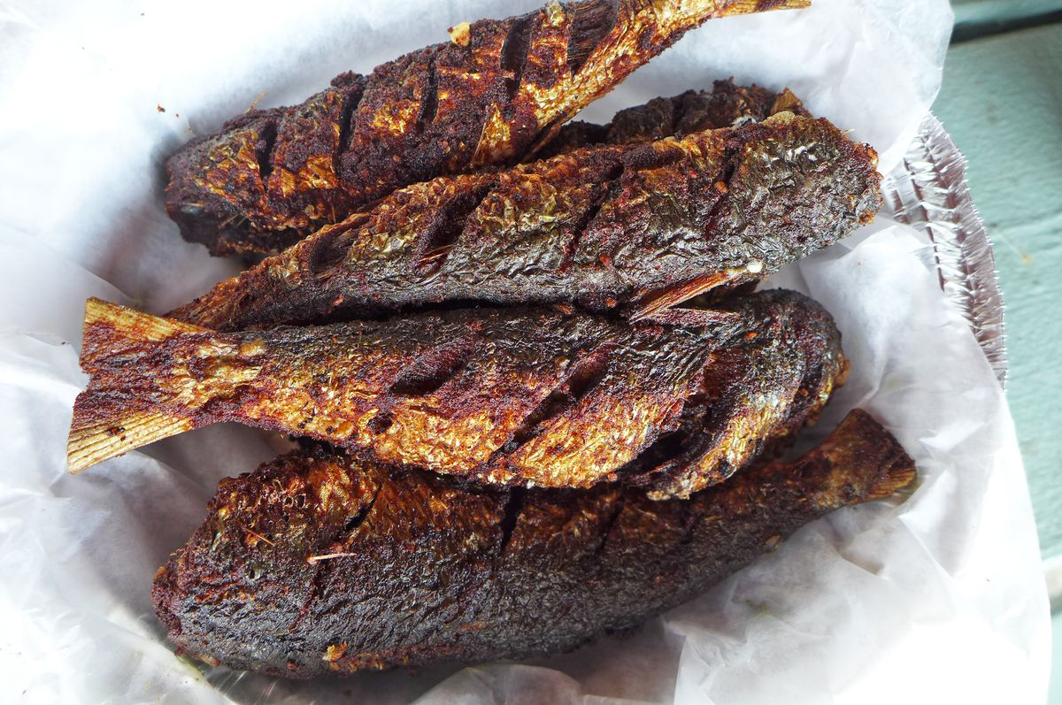 Six small fish slashed on the sides and blackened by flame.