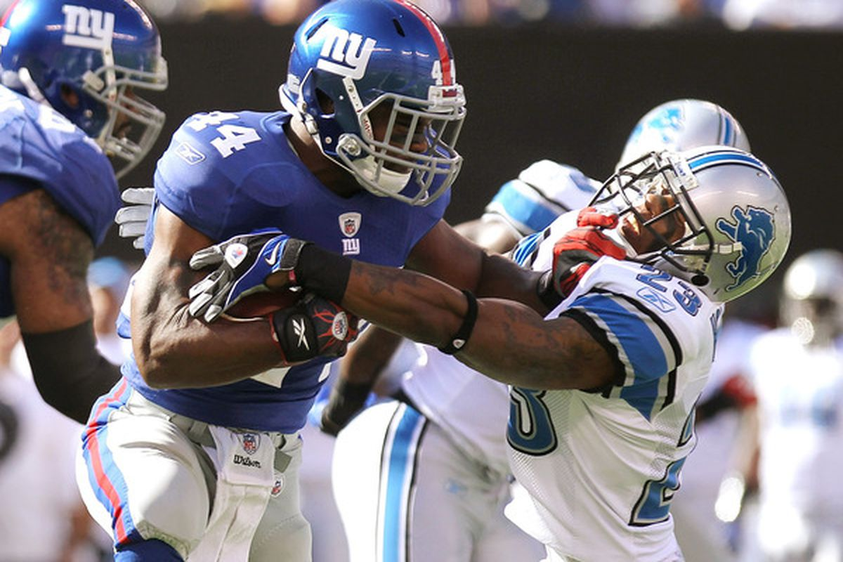 Ahmad Bradshaw (44) of the New York Giants fends off Chris Houston (23) of the Detroit Lions at New Meadowlands Stadium on October 17 2010 in East Rutherford New Jersey.  (Photo by Nick Laham/Getty Images)