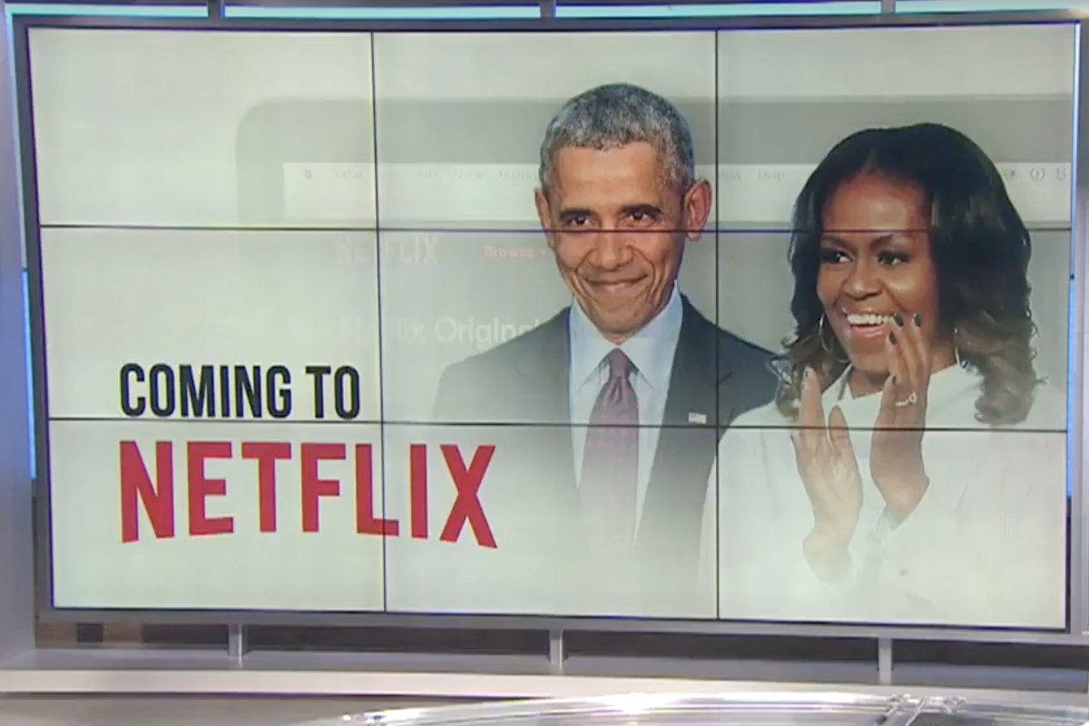 """A large TV screen showing former President Barack Obama and former First Lady Michelle Obama with the words """"Coming to Netflix"""""""