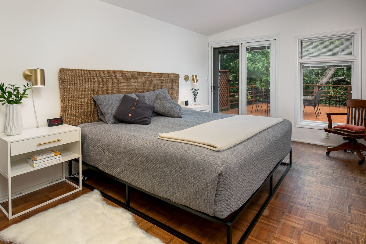 A room with a large bed and a night table with a glass sliding door on the far wall