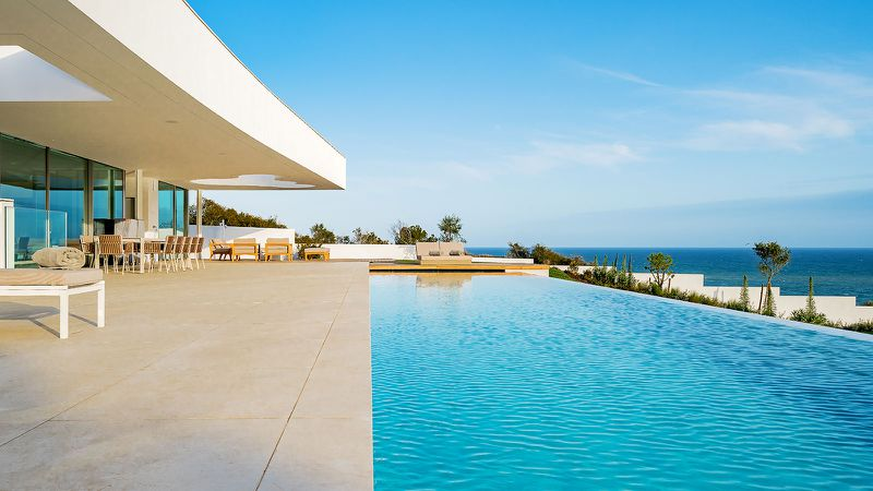An infinity pool is next to a concrete patio.