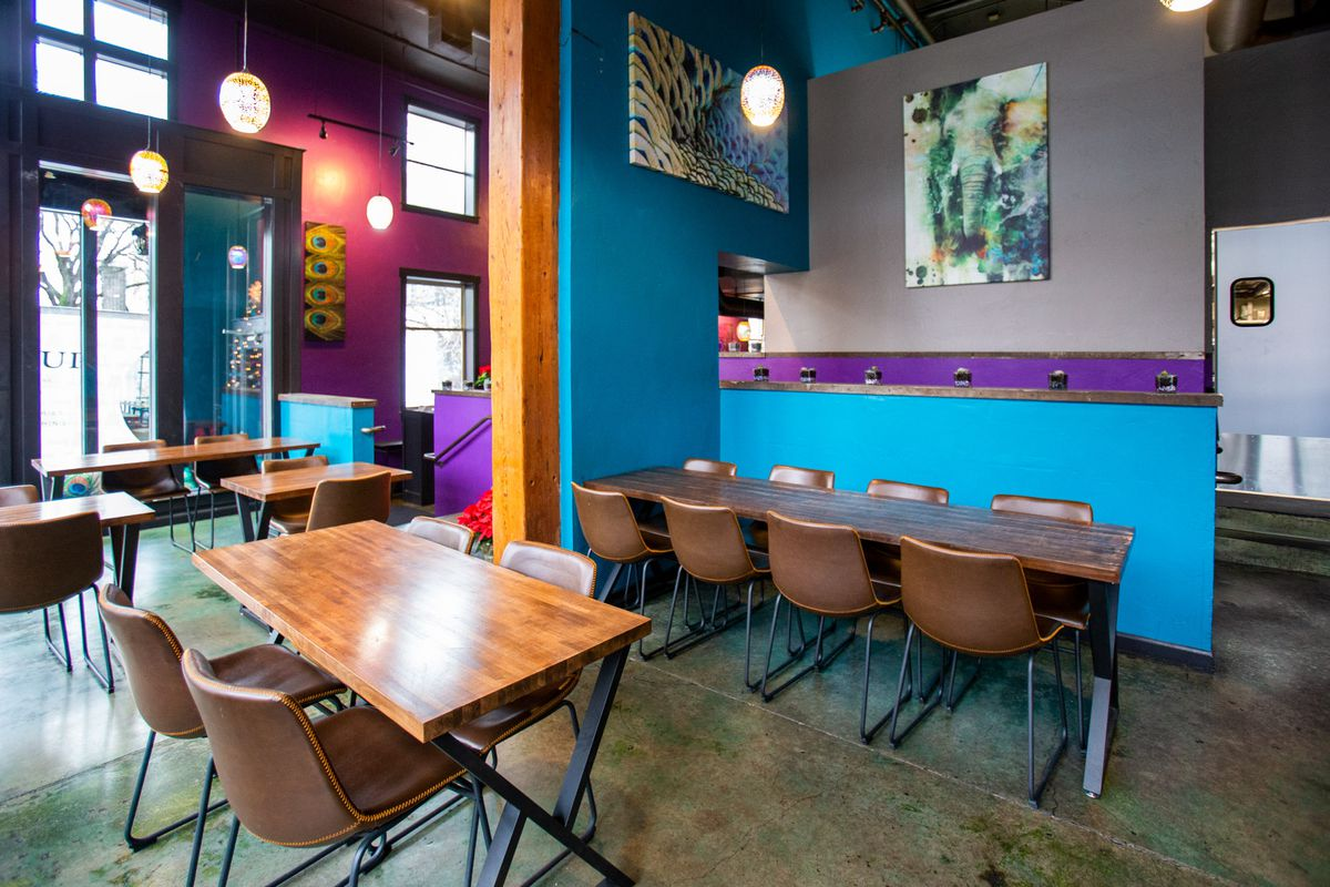 A dining room with abstract paintings on the walls, wooden tables, and lots of blue and purple accents.