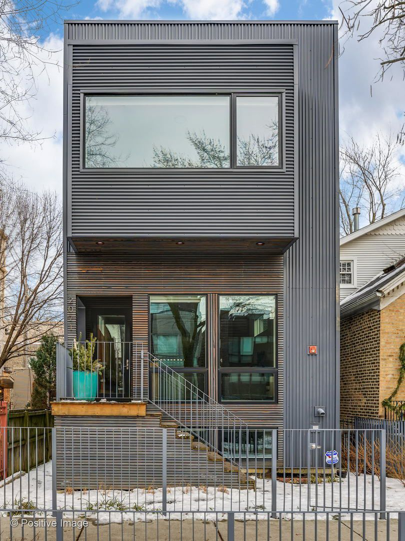 An exterior of the home with corrugated black metal and wood slats.